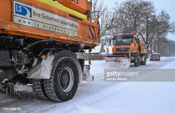 February 2021, Brandenburg, Sieversdorf: Two snowploughs from the winter road maintenance service drive along a village road in the Oder-Spree...