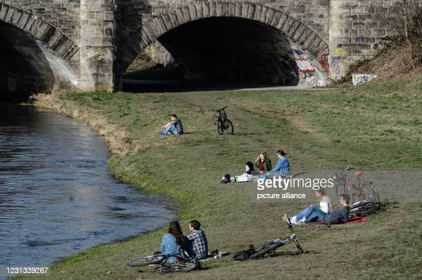 February 2021, Lower Saxony, Göttingen: Young people sit and lie on the banks of the river Leine and enjoy the sun. Photo: Swen Pförtner/dpa