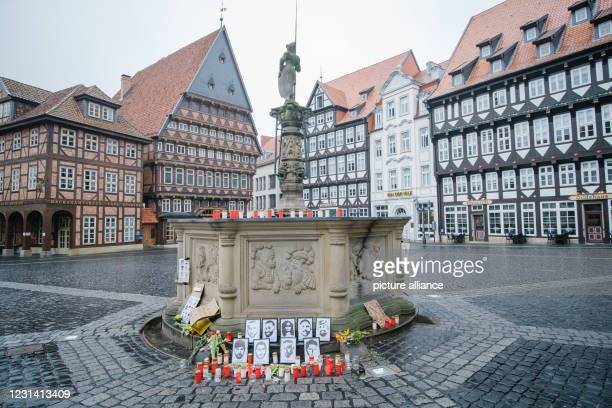 February 2021, Lower Saxony, Hildesheim: Flowers and candles stand in memory of the victims of Hanau in front of the Rolandbrunnen in the city...