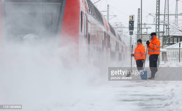 February 2021, Saxony, Leipzig: Service staff clear snow from a platform at Leipzig Central Station with snow pushers. Photo: Jan...