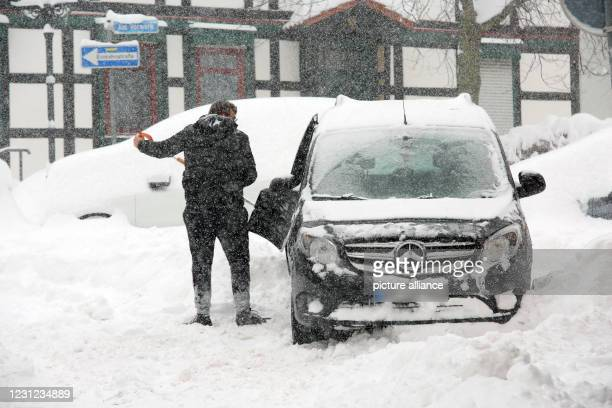 February 2021, Saxony-Anhalt, Wernigerode: Snow-covered vehicles stand at the side of the road in Wernigerode. The winter has parts of Saxony-Anhalt...