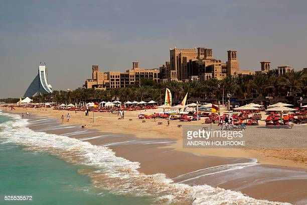 February 23 2012 The luxury hotels Madinat Jumeirah Hotel and the Jumeirah Beach Hotel can be seen on the Dubai Beach Tourists sunbathing