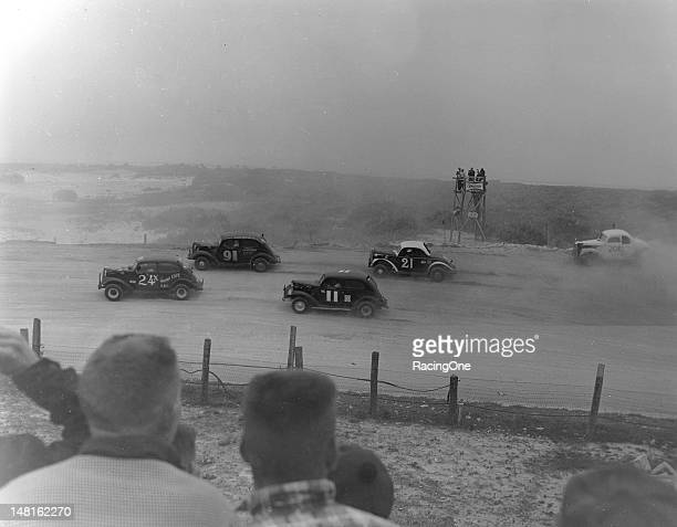 February 25, 1955: Action during the NASCAR Sportsman race on the Daytona Beach-Road Course has James Stultz leading Earl Moss , Wendell Scott , Ray...