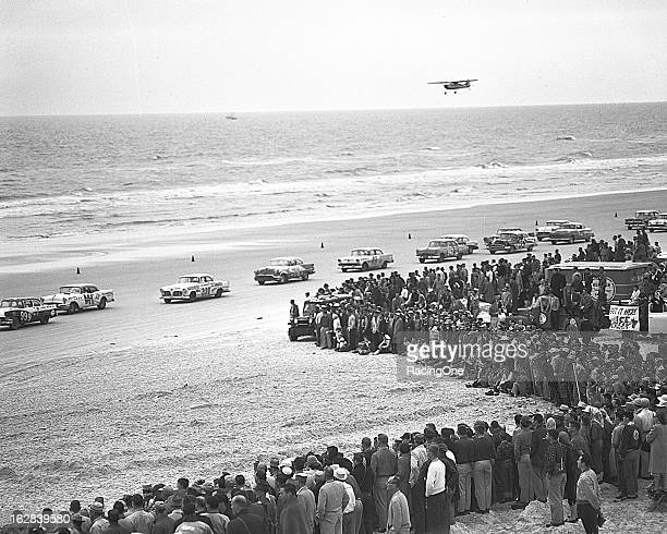 An airplane flies along the beach as a big crowd gathers while cars line up for the start of the NASCAR Cup race on the Daytona BeachRoad Course...