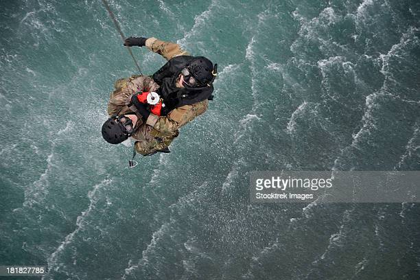 February 26, 2013 - Airmen are hoisted out of the water during a water rescue training scenario off the coast of Torii Station, Japan.