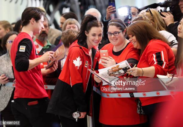 TORONTO ON February 26 Tessa Virtue poses for a selfie with Meghan Freeborn and her mom Sam as Scott signs autographs beside her Many Canadian...