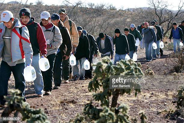 February 28 2007 Sasabe Sonora Mexico Lugging jugs of water migrants thread their way along footpaths leading to the US borderline Backpacks hold...