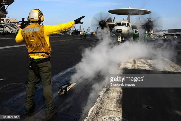 February 28, 2013 - Aviation Boatswain's Mate (Handling) directs an E-2C Hawkeye on the flight deck of the Nimitz-class aircraft carrier USS John C. Stennis.