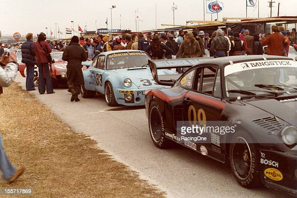 Team members and race fans bundle up against the cold as the field for the 24 Hours of Daytona lines up on pit road at Daytona International Speedway...