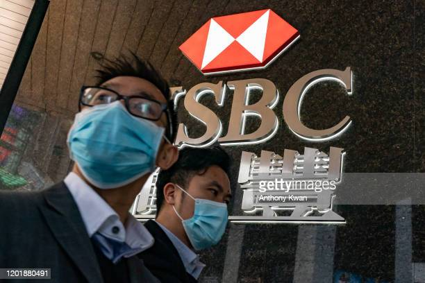 February19: Pedestrians wearing face masks walk in front of a HSBC signage on February 19, 2020 in Hong Kong, China. HSBC Plans to Cut 35,000 Jobs as...