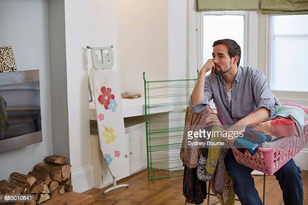 fed up mid adult man with basket of laundry in living room - chores stock pictures, royalty-free photos & images