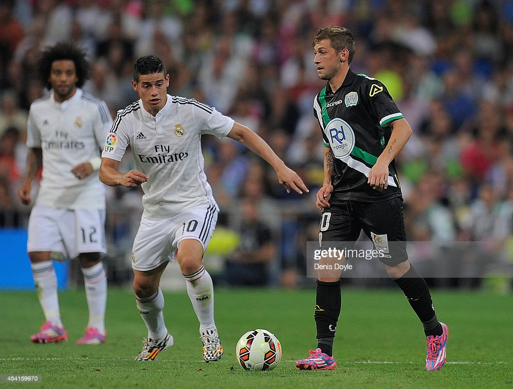 Fede Cartabia of Crodoba CF in action beside James Rodriguez of Real Madrid CF during the La liga match between Real Madrid CF and Cordoba CF at Estadio Santiago Bernabeu on August 25, 2014 in Madrid, Spain.