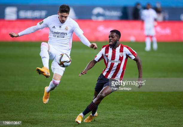 Fede Valverde of Real Madrid competes for the ball with Iñaki Williams of Athletic Club during the Supercopa de Espana Semi Final match between Real...