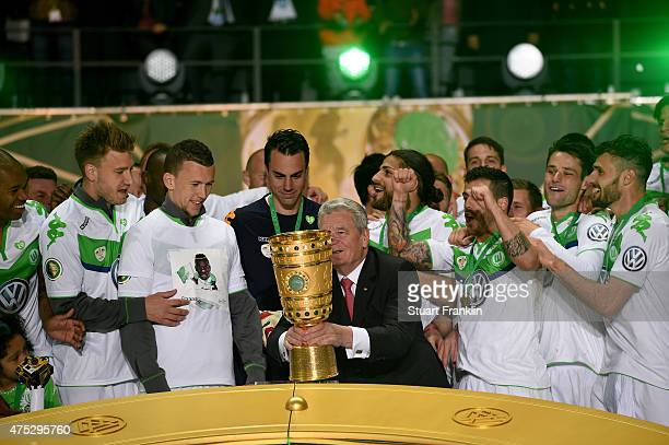 Feder president Joachim Gauck hands over the trophy to team captain Diego Benaglio of VfL Wolfsburg after the DFB Cup Final match between Borussia...