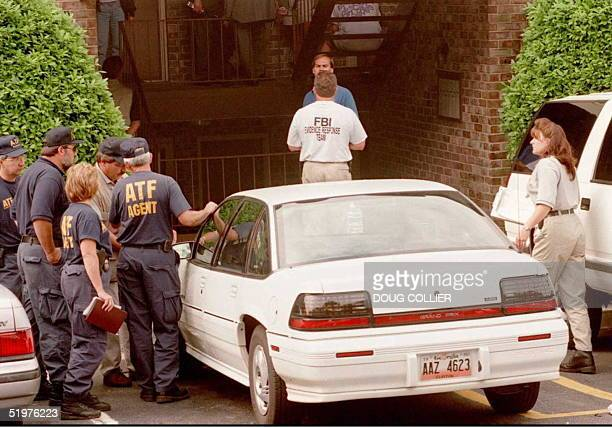 Federal agents gather 31 July outside the home of Richard Jewell the security guard who was working at Centennial Park at the time of the 27 July...