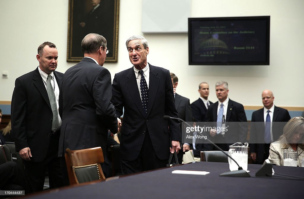 Federal Bureau of Investigation Director Robert Mueller (R) shakes hands with committee chairman Rep. Bob Goodlatte (R-VA) (2L) as he arrives at a hearing before the House Judiciary Committee June 13, 2013 on Capitol Hill in Washington, DC. Mueller testified on the oversight of the FBI.