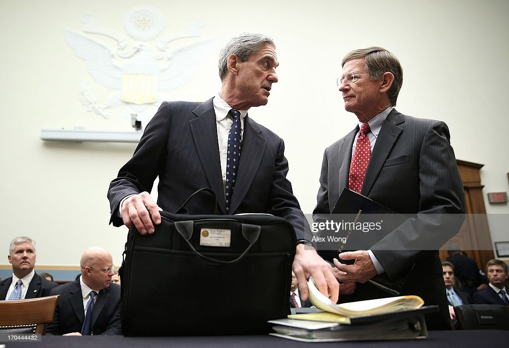 Federal Bureau of Investigation Director Robert Mueller (L) talks to Rep. Lamar Smith (R-TX) (R) as he arrives at a hearing before the House Judiciary Committee June 13, 2013 on Capitol Hill in Washington, DC. Mueller testified on the oversight of the FBI.