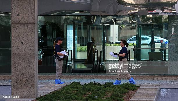 Federal Bureau of Investigation inspect the areas as people visit a growing memorial at the Dallas police department's headquarters following the...