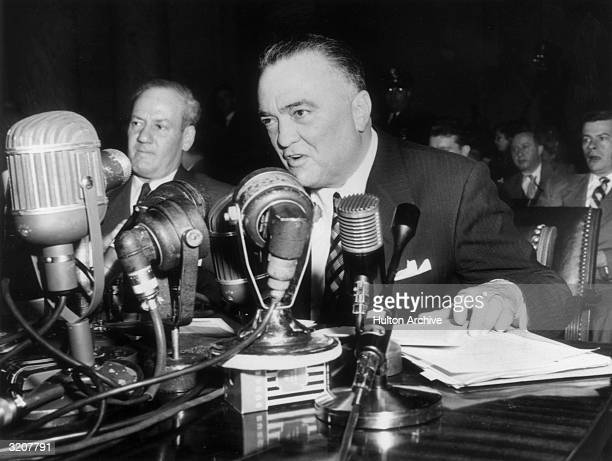 Federal Bureau of Investigations Director J Edgar Hoover sits at a table speaking into several microphones