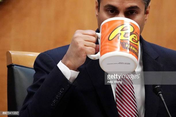 Federal Communications Commission Chairman Ajit Pai drinks from a big coffee cup during a commission meeting December 14 2017 in Washington DC The...