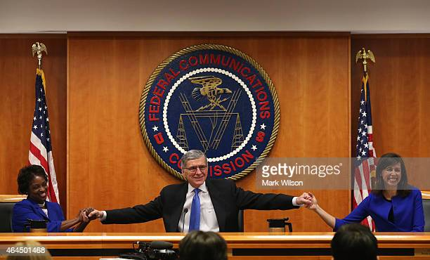 Federal Communications Commission Chairman Tom Wheeler holds hands with FCC Commissioners Mignon Clyburn and Jessica Rosenworcel during an open...