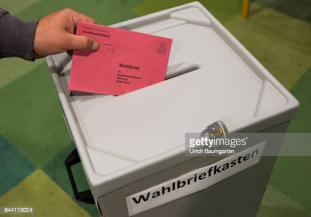 Federal election 2017 Symbol photo on the topic postal vote election elect ballot paper etc Throwing of a postal ballot envelope into a ballot box