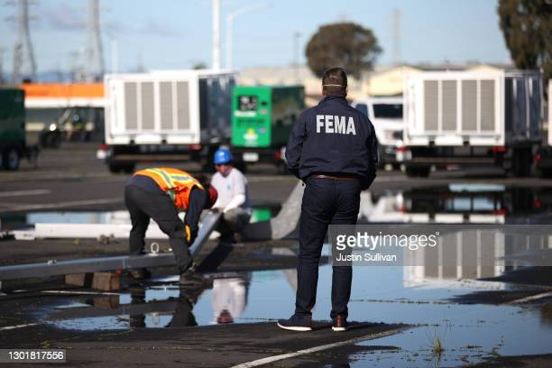 Federal Emergency Management Agency official looks on as workers set up the new mass vaccination site at the Oakland Coliseum on February 12, 2021 in...