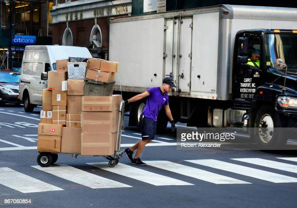 Federal Express deliveryman pulls a cart loaded with packages across a street in New York New York
