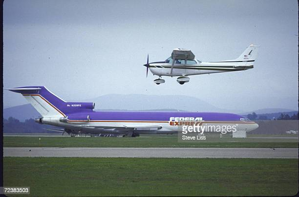 Federal Express jet on runway while Cessna plane lands