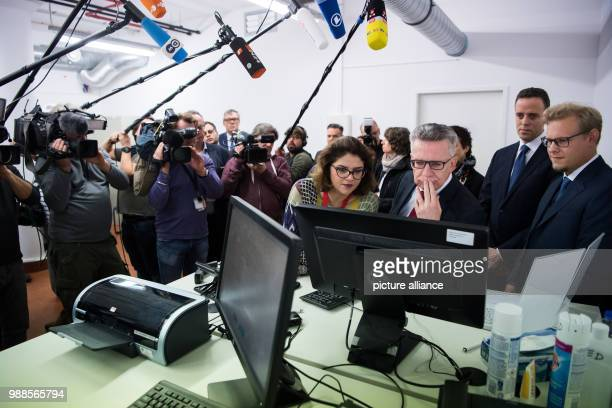Federal interior minister Thomas de Maizière is shown the new identification system by project leader Justus Struebing , head of IT Markus Richter...
