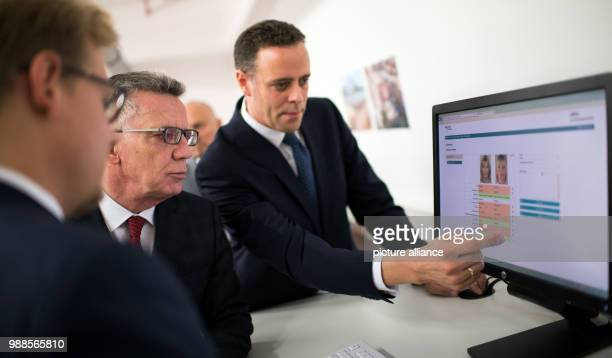 Federal interior minister Thomas de Maizière is shown the new identification system by project leader Justus Struebing and head of IT Markus Richter...