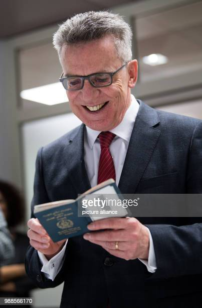 Federal interior minister Thomas de Maizière looks at a falsified ID card at the Federal Office for Migration and Refugees in Berlin, Germany, 6...