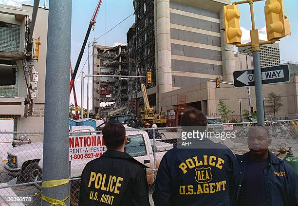 Federal law enforcement agents look 20 April 1995 at the rubble of the Albert P Murrah Federal Building in Oklahoma City one day after a...