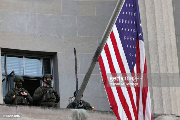 Federal law enforcement officers stand guard at the Department of Justice building on January 17, 2021 in Washington, DC. After last week's riots at...