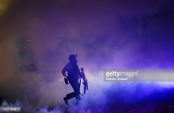 Federal officer runs through tear gas while dispersing a crowd of about a thousand protesters in front of the Mark O. Hatfield U.S. Courthouse on...