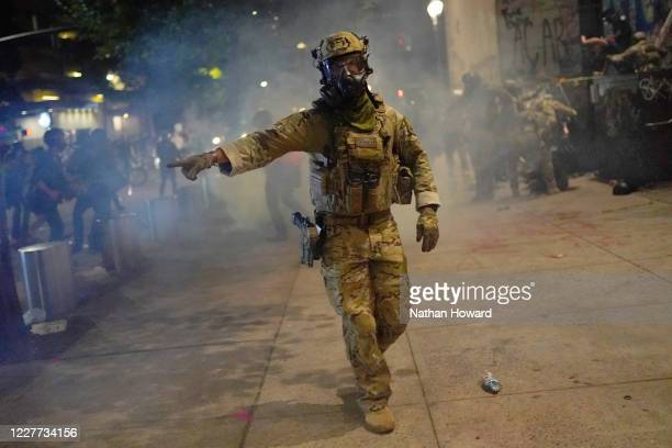 A federal officer tells the crowd to move while dispersing a protest in front of the Mark O Hatfield US Courthouse on July 21 2020 in Portland Oregon...