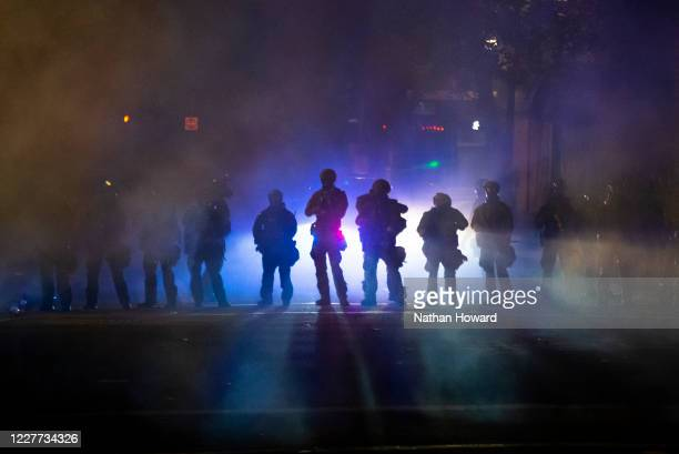 Federal officers walk through tear gas while dispersing a crowd of about a thousand people during a protest at Mark O Hatfield US Courthouse on July...