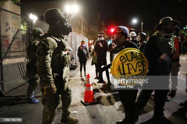 Federal police confront protesters in front of the Mark O Hatfield federal courthouse in downtown Portland as the city experiences another night of...