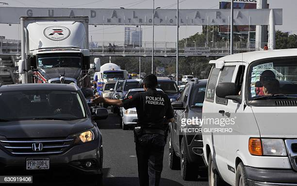 Federal police give instructions to drivers as activists block the GuadalajaraMexico highway during a protest against the rise in fuel prices in...