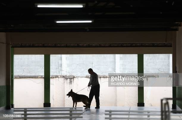 A federal police officer inspects the polling centre where Jair Bolsonaro farright lawmaker and presidential candidate of the Social Liberal Party...