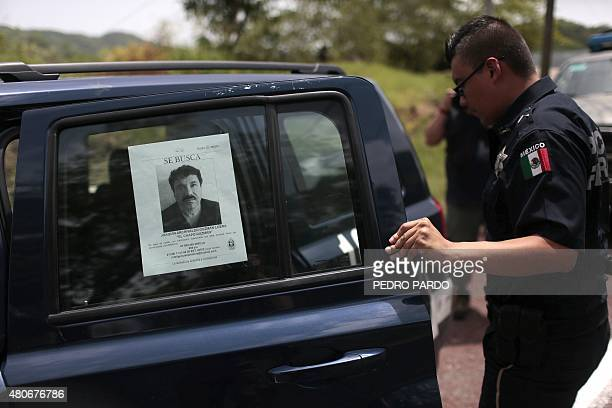 """Federal Police officer opens the door of one of their cars with a picture of fugitive drug lord Joaquin """"El Chapo"""" Guzman's at a checkpoint on the..."""