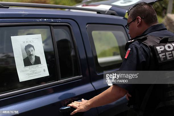 A Federal Police officer opens the door of one of their cars with a picture of fugitive drug lord Joaquin El Chapo Guzman's at a checkpoint on the...