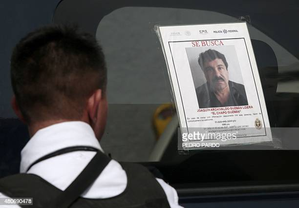 """Federal Police officer stands next to a patrol car with a picture of fugitive drug lord Joaquin """"El Chapo"""" Guzman's on its window, in Acapulco,..."""