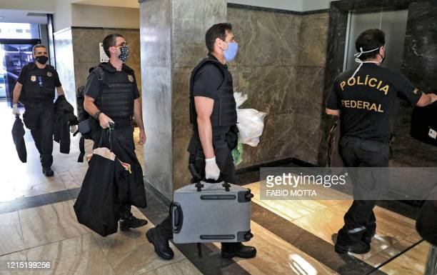 Federal police officers carrying seized evidence walk into the Federal Police headquarters in Rio de Janeiro, Brazil on May 26, 2020. - The Brazilian...