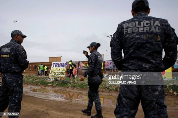 Federal police officers remain near the demonstrators who take part in a protest against US President Donald Trump's migration policies on the...