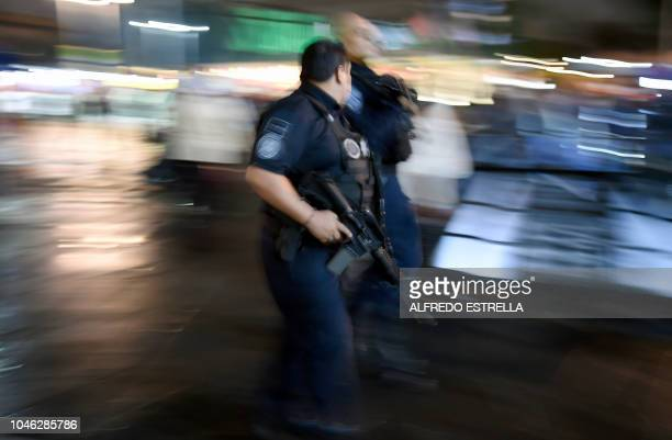 Federal police officers walk on Plaza Garibaldi in downtown Mexico City on October 5 2018 A serenade organized by mariachis and regional Mexican...