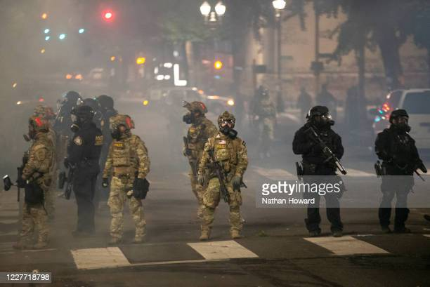 Federal police stand guard on Salmon Street after pushing protesters away from the Mark O Hatfield US Courthouse on July 21 2020 in Portland Oregon...