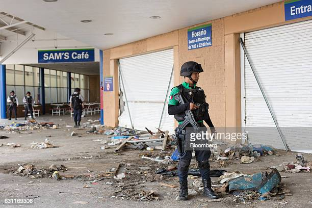Federal police survey the damage at a WalMart Stores Inc location after looting in Veracruz City Mexico on Saturday Jan 7 2017 Mexico's National...