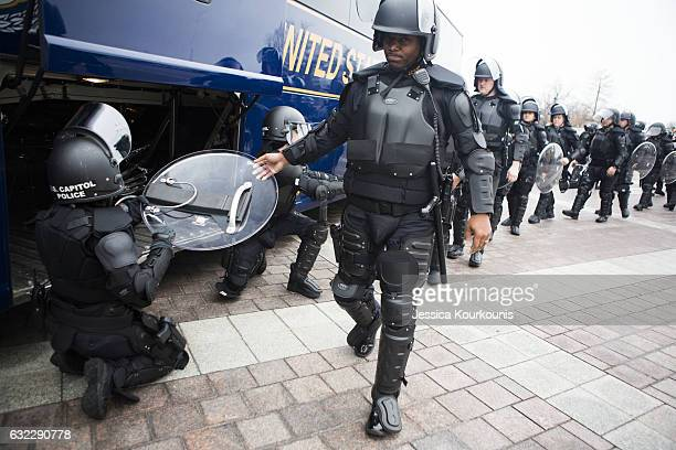 Federal police take off their riot gear before the Women's March on Washington on January 21 2017 in Washington DC Following the inauguration of...