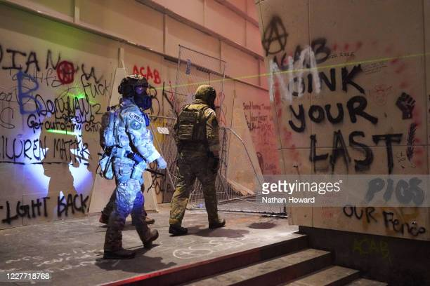 Federal police walk toward the entrance of the Mark O Hatfield US Courthouse while a protester shines a laser in their direction on July 20 2020 in...
